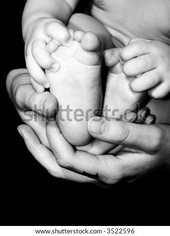 An infants feet being held in the loving hands of mother.