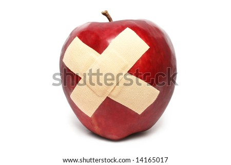 An injured red apple with plaster on it. - stock photo