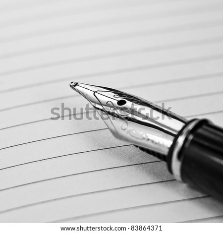 An ink pen on a lined paper - stock photo