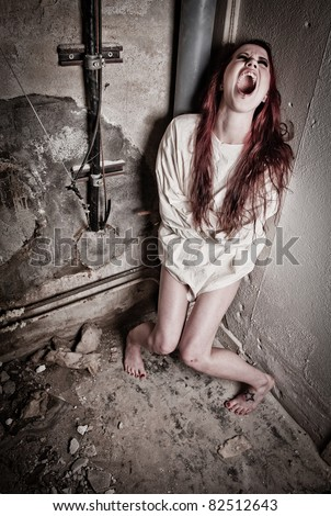 an insane psycho girl wearing a straight jacket - stock photo