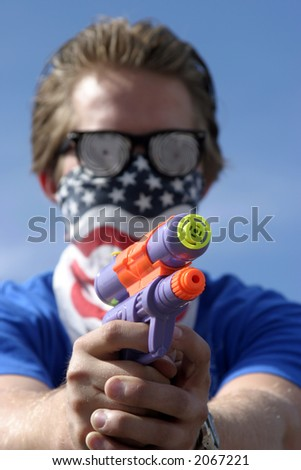 an insane young man wearing Hypnoitic Glasses and an American Flag bandanna holds a Squirt Gun - stock photo