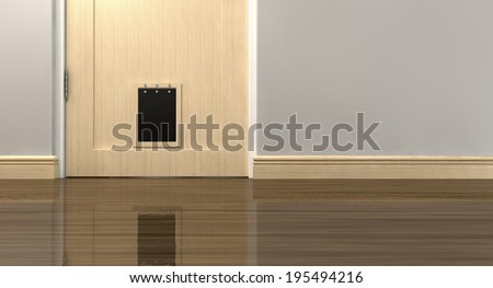 An inside view of a regular black pet flap on a light wood door surrounded by walls and wood skirting