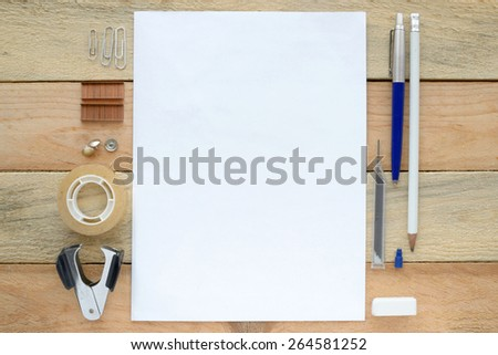 An inspirational wooden office table with a notepad, pencils and some supplies viewed from above with copy space - stock photo