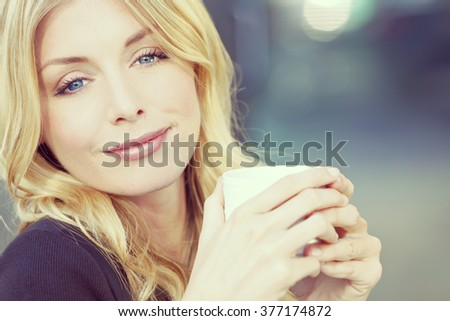 An Instagram filter style portrait of a beautiful smiling young woman with blond hair and blue eyes drinking coffee or tea from a white cup - stock photo