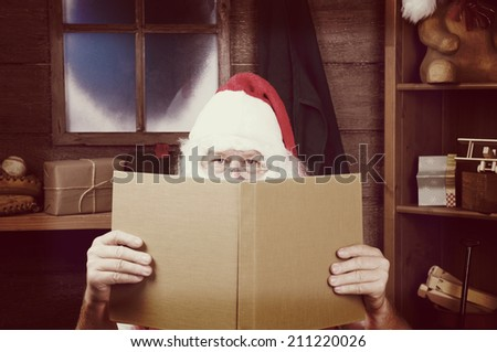 An Instagram style Santa Claus Sitting in His Workshop peering over the top of a large book. Horizontal Composition - Focus on Santa's eyes, slight reflection in window.