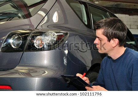 An insurance agent inspecting a car. - stock photo