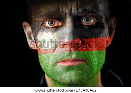 An intense stare from a man with their face painted with the Afghanistan flag.