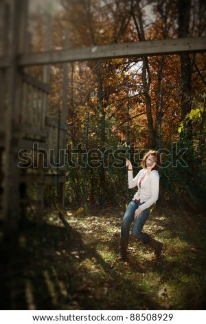 An intentional blur/selective focus of a woman on a swing - stock photo