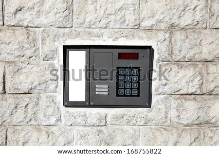 An intercom doorbell and access code panel on the wall. - stock photo