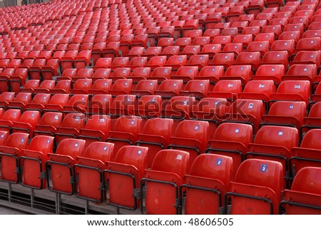 An interesting angle of folded arena red seats. - stock photo
