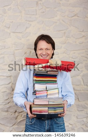 An interior decorating expert carries a high stack of paint, wallpaper and fabric samples in his arms, upper body smiling portrait against a wall with copyspace - stock photo