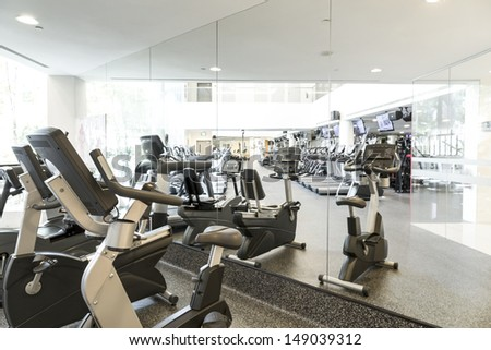 An interior shot of a club gym with all the execrise equipments - stock photo
