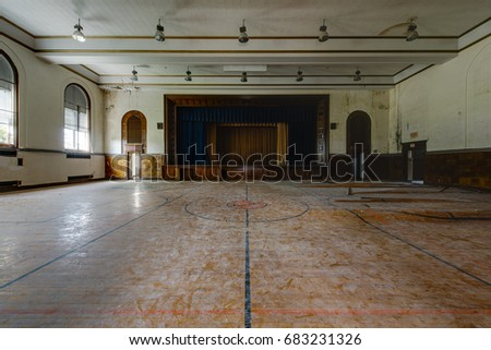 An interior view of a derelict gymnasium and stage with a gorgeous hardwood floor at an abandoned school.