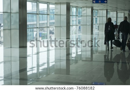 An interior view of passengers walking along a corridor of a busy international airport. - stock photo