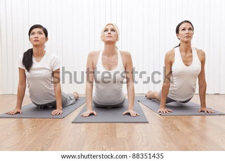 An interracial group of three beautiful young women stretching in a yoga position at a gym - stock photo