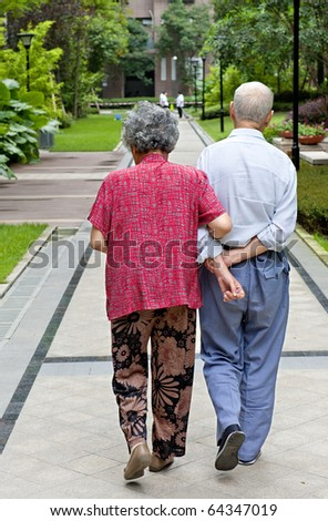 an intimate senior couple are walking - stock photo