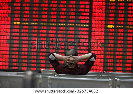 An investor watchs electric board in a stock market in Huaibei, Anhui province, east China on 12th October 2015.  - stock photo