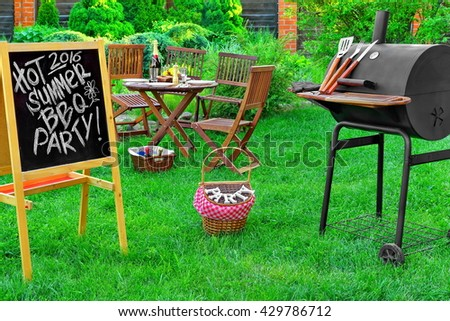 An Invitation To A Summer Barbecue Grill Party 2016, Written on Blackboard, Barbecue Charcoal Grill Appliance And Outdoor Wooden Furniture On The Backyard Lawn In The Background - stock photo