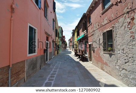 An inviting backstreet between brightly painted houses in a European urban area - stock photo