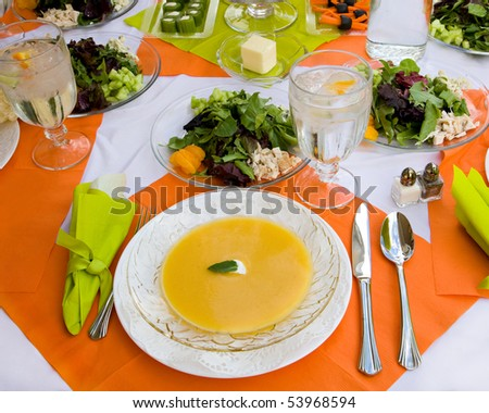 An inviting table is set beautifully and colorfully with nice dishes and a healthy meal. - stock photo