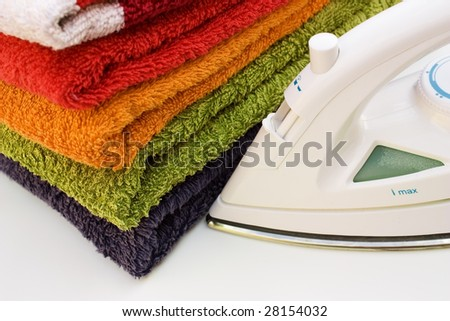 An iron with a stack of colorful towels on a white background. - stock photo