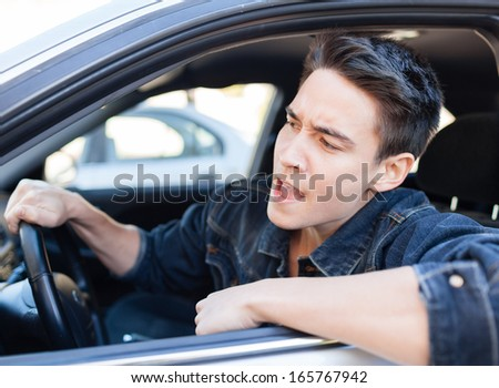 An irritated young man driving a vehicle is expressing his road rage.  - stock photo