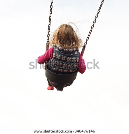 An isolated girl swinging high on a swing - stock photo