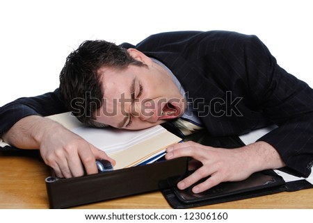An isolated on white shot of a businessman resting his head on desk yawning. - stock photo