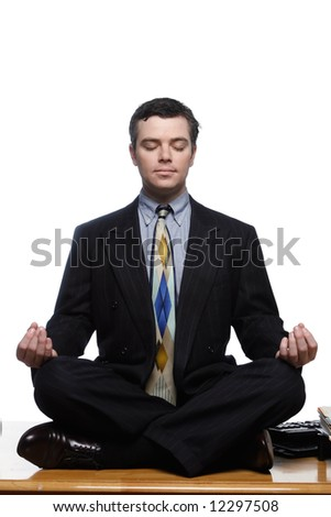 An isolated on white shot of a businessman sitting on desk in a yoga pose. - stock photo