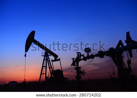 An isolated operation of pumping unit, in the field of the setting sun  - stock photo