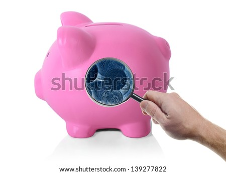 an isolated pink piggy bank looking inside with magnifying glass x-ray vision on white background - stock photo