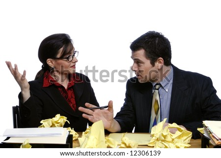 An isolated shot of a businessman and businesswoman discussing ideas at a desk, littered with yellow paper. - stock photo