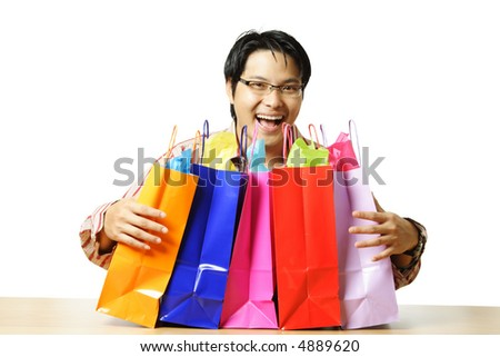 An isolated shot of a happy young man with shopping bags and gifts - stock photo