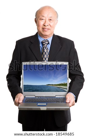 An isolated shot of a senior asian businessman carrying a laptop (Note: image on the laptop is taken by me) - stock photo