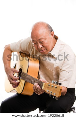 An isolated shot of a senior asian man playing guitar - stock photo