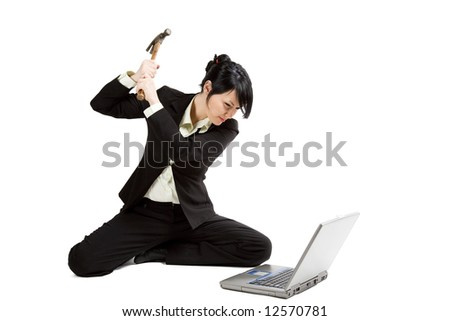 An isolated shot of an angry and stressed businesswoman smashing her laptop with a hammer - stock photo