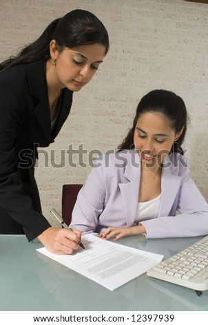 An isolated shot of two businesswomen signing a contract. - stock photo