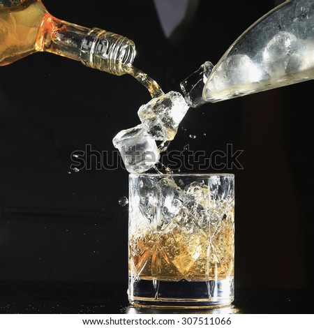 An isolated shot of whiskey with a splash on a black background - stock photo