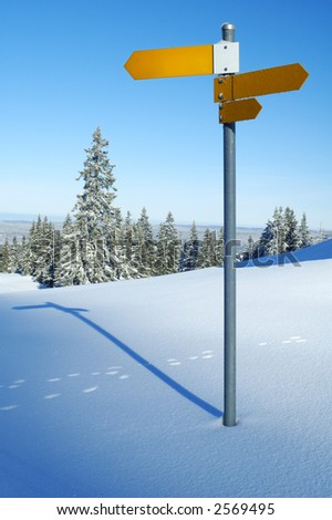 An isolated signpost, in snowy mountains, space for text on the sign, or in the sky. - stock photo