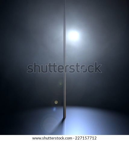 An isolated stripper pole on a stage lit by a single spotlight on a dark background
