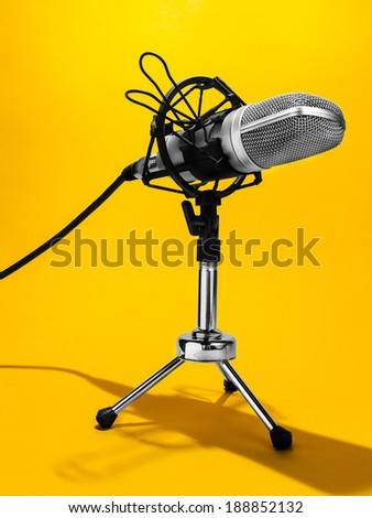 An isolated studio microphone on a yellow background  - stock photo