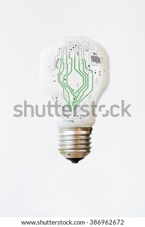 An isolated white light bulb with green, electronic lines surging through the middle. Vertical  - stock photo