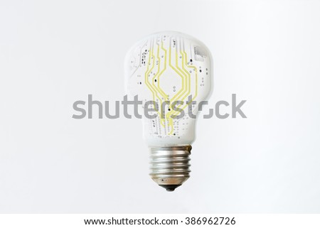 An isolated white light bulb with yellow, electronic lines surging through the middle. Vertical  - stock photo