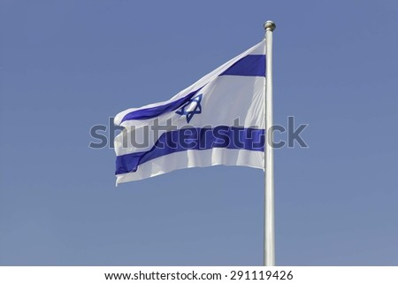 An Israel flag flapping in the wind isolated on blue sky background. The flag is in white and blue colors with the star of David. The flag is posted on a pole high in the sky. - stock photo