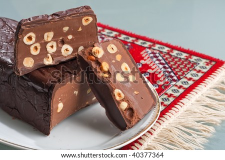 An Italian Chocolate Torrone candy block with hazelnuts, dark chocolate and milk chocolate on a white dish over a red rug - stock photo