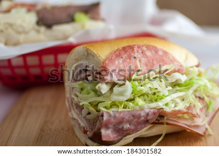 An Italian submarine sandwich in a red plastic basket. - stock photo
