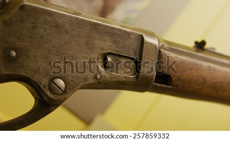 An 1881 lever action rifle with a broken fore stock and lots of scratches from use.  This is an original gun. - stock photo