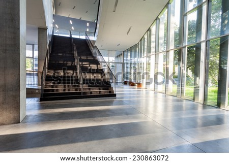 an long corridor in large building with stairs and glass - stock photo