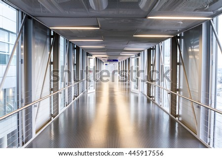 an metal corridor with glass in order to go to the plane