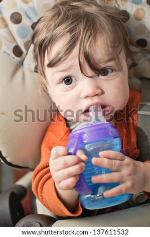 An 11 month old baby with a sippy bottle.